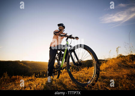 Male biker looking away while sitting on bicycle against sky - Stock Image