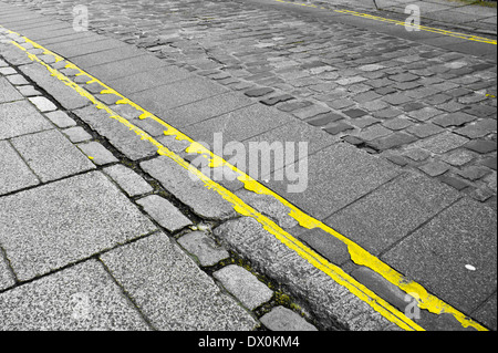 Double yellow lines on a cobbled street in England - Stock Image