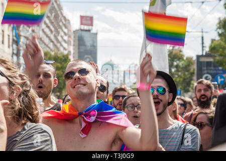 BELGRADE, SERBIA - SEPTEMBER 17, 2017:  Picture of young men waiving rainbow gay flags in the middle of the crowd during the Belgrade Gay Pride. The p - Stock Image