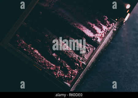 palette with crushed powder eyeshadows in nude and blush tones on dark background shot with moody lighting, concept of beauty and make-up trends - Stock Image