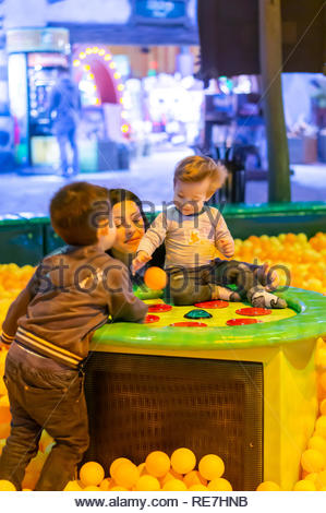 Kownaty, Poland - January 6, 2019: Woman playing with boy and toddler on a playground with a machine and plastic balls in the Majaland indoor amusemen - Stock Image