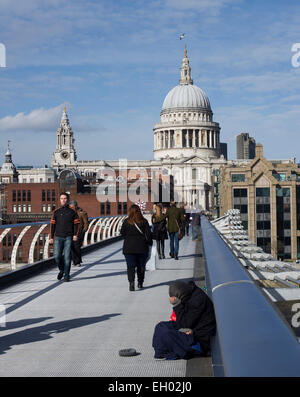 The Millennium bridge is a cold place for one of London's down-and-outs to go about his business - Stock Image