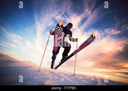 Low angle view of skier jumping on snow against sky - Stock Image