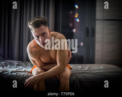 Shirtless naked sexy male model sitting alone on his bed in his bedroom, looking at camera with a seductive attitude - Stock Image