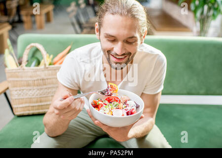 Handsome man eating healthy salad sitting indoors on the green sofa with bag full of vegetables on the background. Healthy eating concept - Stock Image