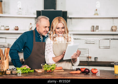 happy woman using digital tablet while standing with husband in kitchen near vegetables - Stock Image