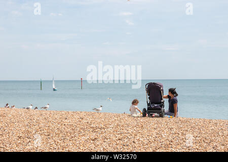 A mother and her young daughter sitting on the pebbles in a british beach enjoying the sun at the seaside - Stock Image
