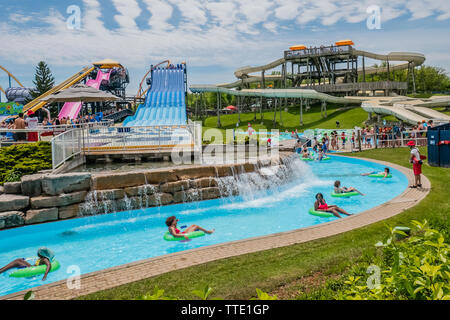 people enjoying a hot summer afternoon inside a waterpark - Stock Image