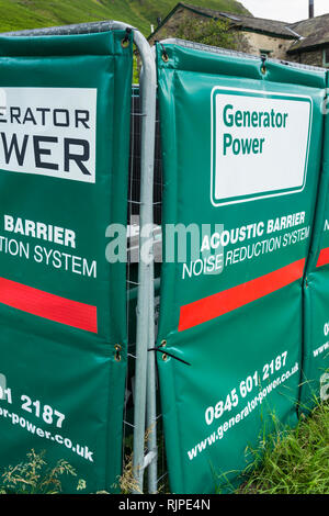 Temporary acoustic barrier surrounding a large portable electricity generator sited outside an isolated rural building in the Lake District. - Stock Image