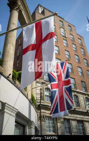 Union Jack and flag of St. George outside the Grosvenor House Hotel on Park Lane, London - Stock Image