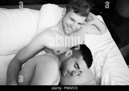 Handsome naked gay couple in bed with one sleeping on his partner's belly as the other smiles - Stock Image