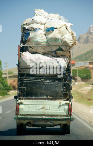 Fully laden vehicle transporting produce, Iran - Stock Image