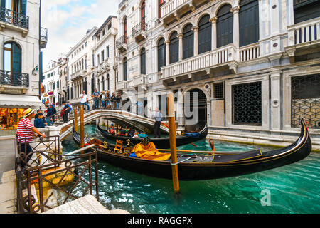 A busy section of canal at the calle de la canonica as tourists cross the bridge over gondola and a gondolier waits for customers in Venice, Italy - Stock Image