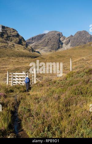 Hill walker approaches deer fencing below Bla Bheinn (Blaven) in the Black Cuillin Mountains on the Isle of Skye, Scotland, UK - Stock Image