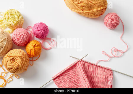 Knitting project in progress. A piece of knitting with ball of yarn and a knitting needles. - Stock Image