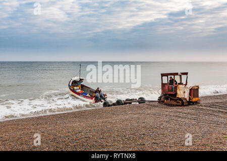 Fishermen on Salthouse beach, in Norfolk launch their boat just after dawn. - Stock Image