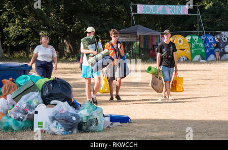 Festival goers leave Henham Park the morning after the end of Latitude Festival 2018 among piles of rubbish. - Stock Image
