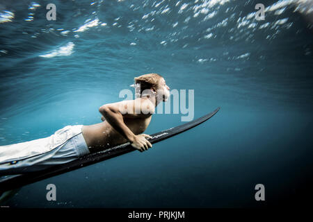 Underwater view of surfer duck diving under wave in Sumatra, Indonesia - Stock Image