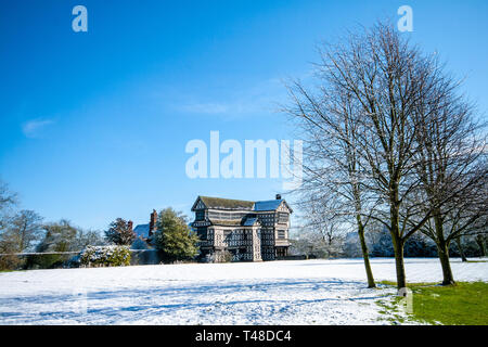 Little Moreton Hall a Tudor manor house owned by the National Trust  near Congleton Cheshire England in the snow as seen from the south Cheshire way - Stock Image