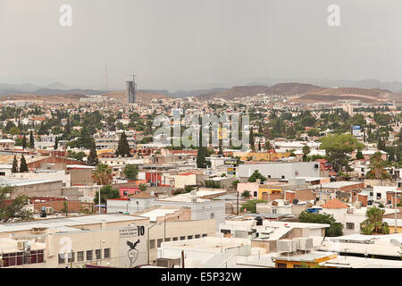 Elevated city view of downtown Chihuahua City, Chihuahua, Mexico with mountains and tall building being built in - Stock Image