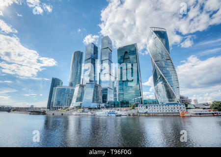 Skyscrapers of Moscow city on the river bank with reflection of clouds on the glass of buildings - Stock Image