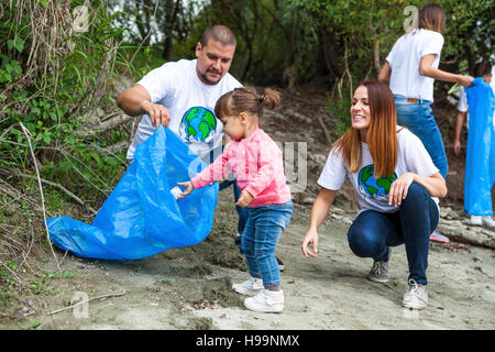 Family and volunteers doing garbage cleanup in park - Stock Image