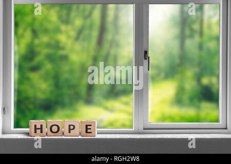 Hope sign in a window sill with a view to a green forest in sunlight - Stock Image