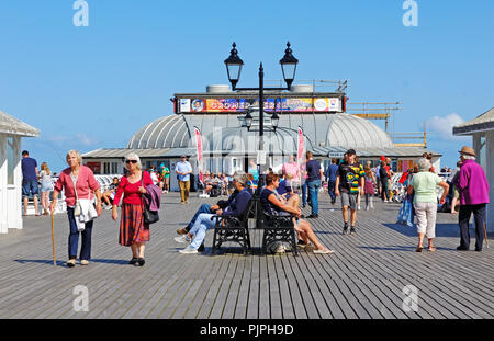 People enjoying a sunny summer afternoon on the Pier at the North Norfolk seaside resort of Cromer, Norfolk, England, United Kingdom, Europe. - Stock Image
