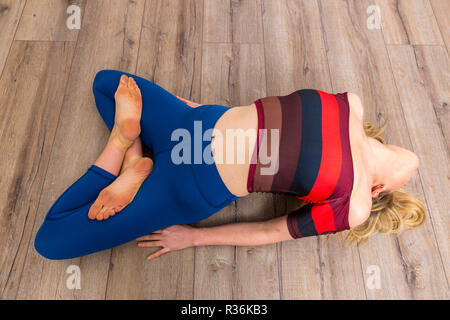 Woman with long blond hair doing yoga exercises - Stock Image