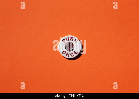 Push once button on orange background - Stock Image