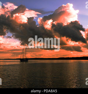 Summer sunset with predominately cumulonimbus clouds against a steel blue sky reflected in ocean water. Fraser Island, Queensland, Australia. - Stock Image