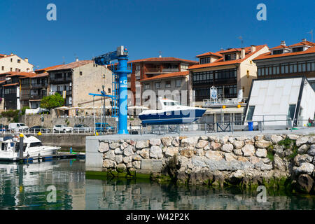 Fishing port with boats anchored to the shore in village of Llanes, Principality of Asturias, Spain. - Stock Image