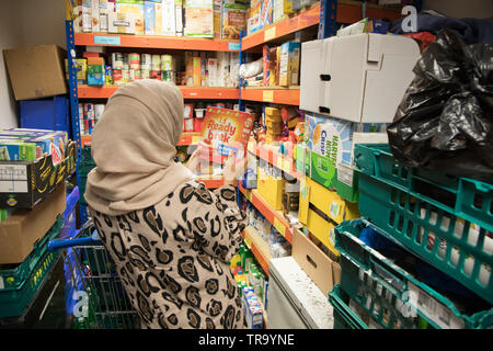 A Muslim woman with a headscarf packing bags at a foodbank - Stock Image