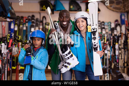 Happy cheerful positive  African man and European woman with preteen son standing with purchased ski equipment in shop - Stock Image