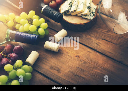 wine bottles with grapes and cheese on wooden background. copy space - Stock Image
