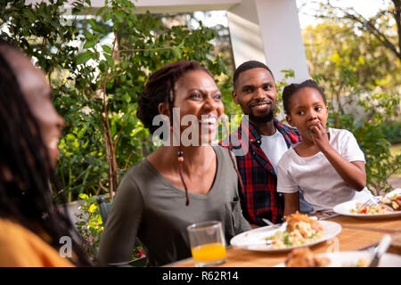 A family eating lunch together on a patio - Stock Image