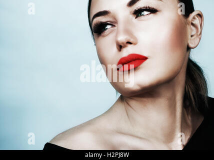 Closeup portrait of a beautiful woman over blue background, attractive model with sexy red lips and perfect evening - Stock Image