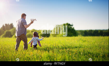 Boy playing in aviator hat with old plane - Stock Image