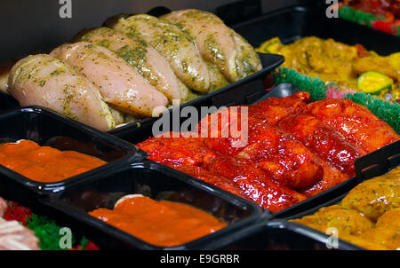 Fresh chicken fillets marinaded in chinese coatings on a Butchers display counter for making your own easy stir - Stock Image