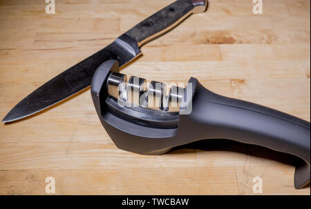 Closeup of a modern, carbide cutting head, knife sharpener, resting on a wooden surface, with a steel kitchen knife alongside. - Stock Image