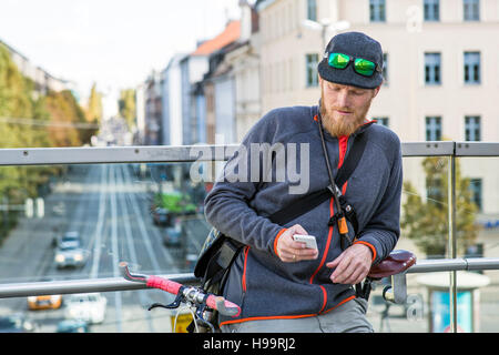 Bike messenger looking at smartphone - Stock Image