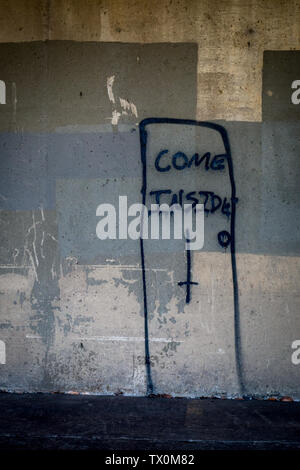 A door with an upside down cross and the words 'Come Inside' painted on a dirty wall - Stock Image
