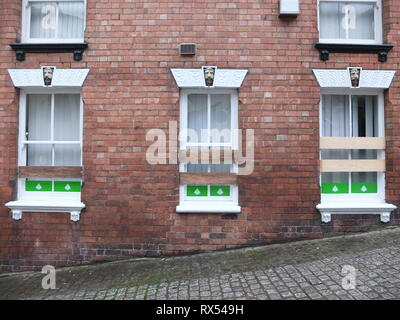 Ashbourne Shrovetide Football 2019. Windows of the Leek Building Society with Victorian bearded man detail boarded up prior to Ash Wednesday game. - Stock Image