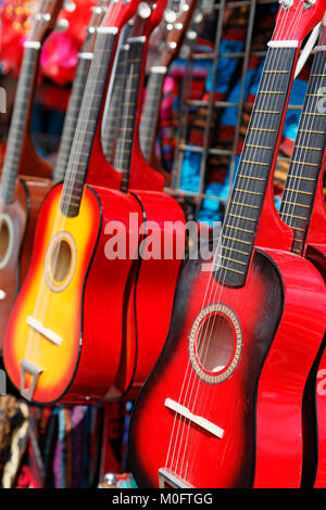 Red guitars for sale at a festival. - Stock Image