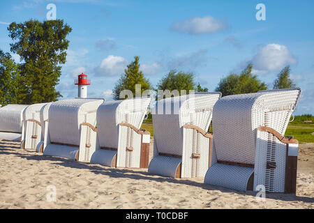 Wicker chairs on an empty beach on a sunny day. - Stock Image