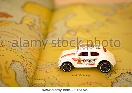 Mattel Hot Wheels toy classic Volkswagen Beetle car on a map page from a open atlas book in soft focus on circa June 2019 in Poznan, Poland. - Stock Image