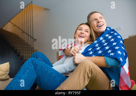 happy couple looking up while wrapping in usa national flag - Stock Image