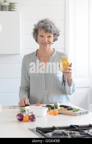 Happy woman preparing food in kitchen - Stock Image