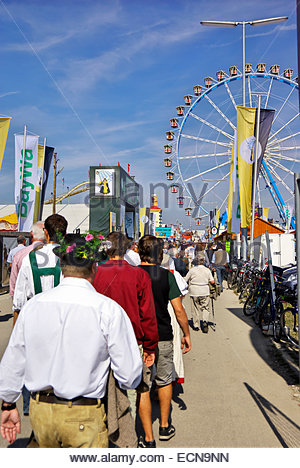 Visitors to Oktoberfest walk past booths and rides. - Stock Image