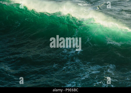 Detail of crashing waves, surf and crest, windblown mist curling from the white water, and deep green ocean water. - Stock Image